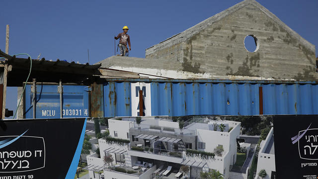 A Palestinian works on a new housing project in the West Bank settlement of Naale