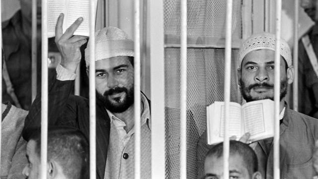 Khalid al-Islambouli, left, and Abdel Hamid Abdel Aal hold up open Qurans during the second day of their trial in Cairo, Egypt, Monday, Nov. 30, 1981