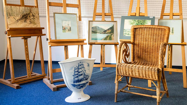 A picture taken on February 8, 2019 at the Weidler auction house in the southern German city of Nuremberg shows a wicker armchair, bearing a swastika, a vase and watercolours which are presumed to have belonged to late Nazi dictator Adolf Hitler. (Photo: AFP)