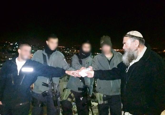 Honenu CEO Shmuel Meidad handing out the NGO's calling cards to Border Policemen