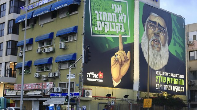 A billboard shows Hezbollah leader Nasrallah as the face of a satirical eye-catching, plastic bottle recycling campaign