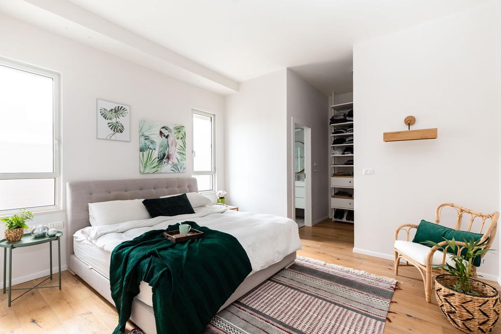 האם  אוהבת ירוק, צבע שמסמל עבורה את הטבע, ולכן הוא שב ומופיע בחדרי הבית, כולל בחדר ההורים: בציורים שמעל המיטה, בריפוד כרית הכורסה ובכיסוי המיטה (צילום: אורית ארנון)