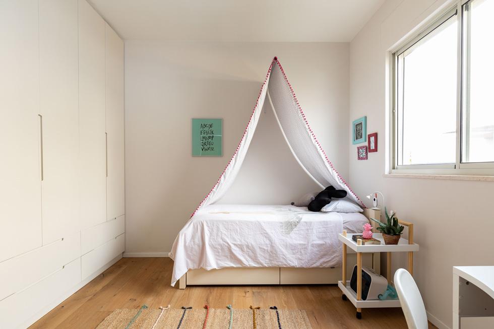 """חדרי השינה מעוצבים בפשטות. המיטה של הבת הבכורה מוגבהת, כך שתוכל להיכנס אליה יותר בקלות. """"במהלך העבודה"""", אומרת המעצבת, """"הידקנו את התכנון עוד ועוד, כדי לדייק את מכלול הצרכים ולמצוא להם פתרונות מיטביים - פונקציונאליים ואסתטיים כאחד""""   (צילום: אורית ארנון)"""