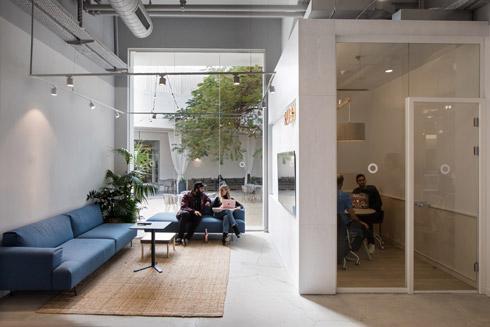 ביתני עץ בהירים משמשים כחדרי ישיבות קטנים לצוותים השונים. ליד כל ביתן עוצב סלון קטן, שקוף כלפי החצר (צילום: שירן כרמל)