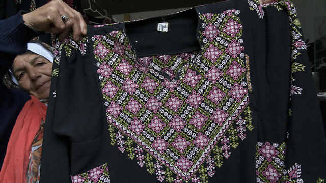 Samiha Jeheshat, displays a handmade embroidered Palestinian thobe at her showroom in the West Bank village of Idna, north of Hebron