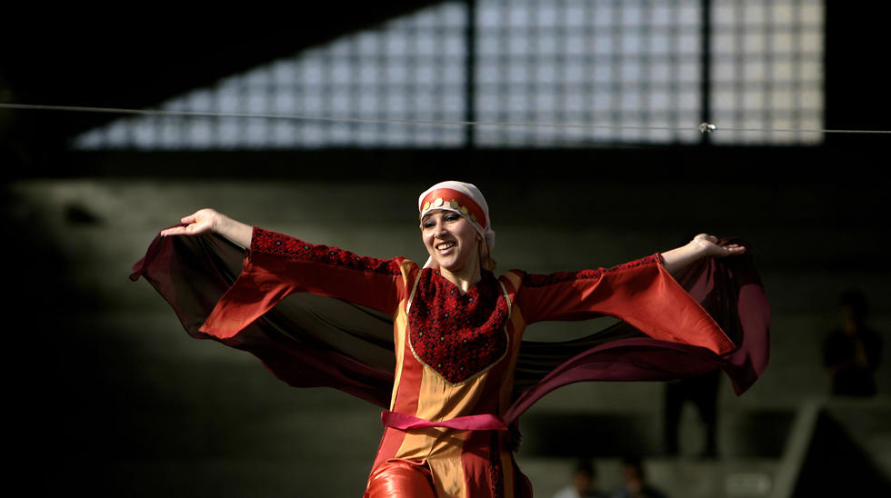 Palestinian woman wearing a Palestinian dress with traditional embroidery performs a folk dance known as Debka, during a folk festival in the West Bank city of Ramallah