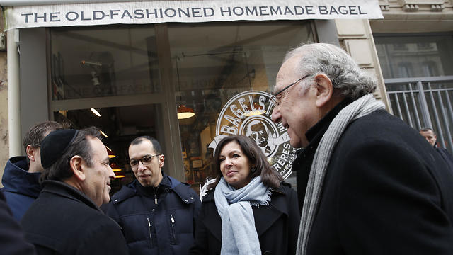 """Paris mayor Anne Hidalgo, second right, talks with the President of the Central Jewish Consistory of Paris Joel Mergui, left, as district mayor Pierre Aidenbaum, right, looks on outside the bagel shop which was sprayed with the German word """"Juden"""" on its front window last week, in Paris, Tuesday, Feb.12, 2019."""