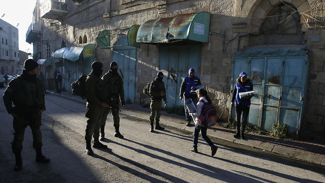 Palestinian observers, right, watch as children walk past Israeli soldiers on their way to school in the West Bank city of Hebron