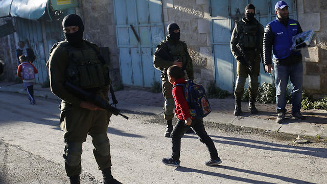 A Palestinian observers, right, watches as children walk past Israeli soldiers on their way to school in the West Bank city of Hebron