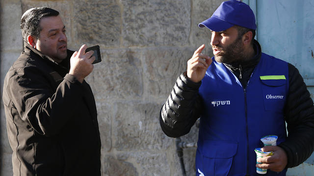 Israeli settler, left, takes a picture of a Palestinian observer as he watches over children walking to school in the West Bank city of Hebron
