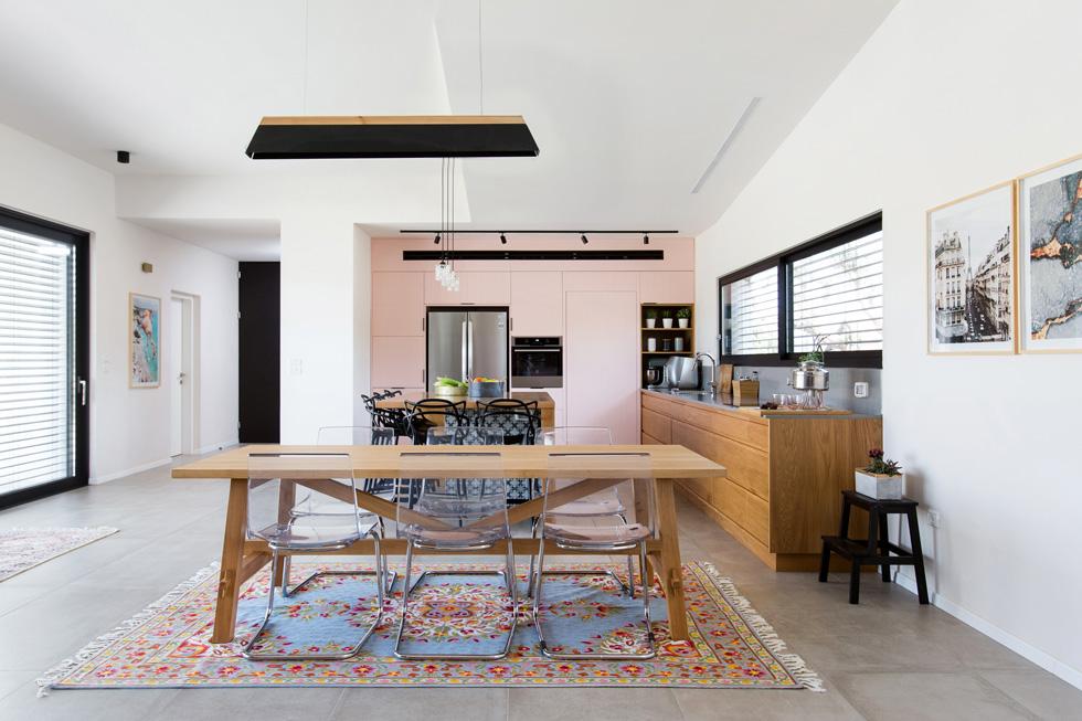"""מבט אל קיר הארונות הוורודים במטבח (משמאל נראית המבואה). רוב התקציב הוצא על האדריכלות, ומעצבות הפנים עבדו עם מה שנשאר. """"בניגוד לדירות במרכז הארץ"""", הן אומרות, """"התפיסה פה היא של מרחבים, בלי אילוצים של גודל"""" (צילום: שירן כרמל)"""