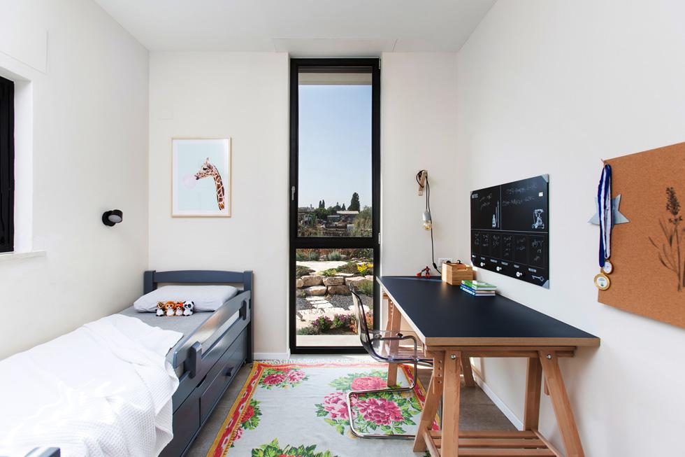 """חדרו של אחד מהבנים הצעירים. החלון פונה אל הגינה והנחלה המשפחתית, ובפנים, אומרות המעצבות, """"חומרי גמר לא יקרים ורהיטי איקאה"""" (צילום: שירן כרמל)"""