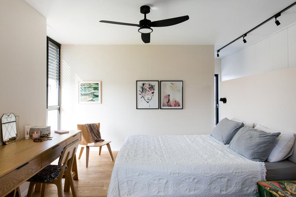 המיטה בחדר ההורים נשענת על קיר נמוך. מולה שולחן עץ ארוך, המשמש גם כשולחן עבודה. הפרקט נרכש, לדברי המעצבות, במבצע, וההדפסים שעל הקירות נבחרו ונרכשו באינטרנט ומוסגרו בארץ (צילום: שירן כרמל)