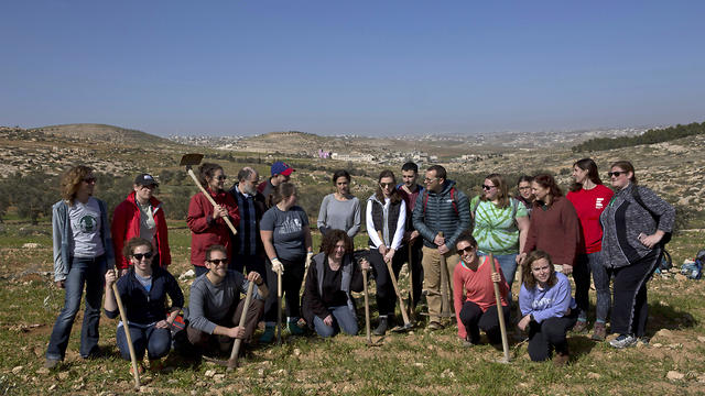 American rabbinical students take a group photo, with the village of Attuwani in the background, during a day planting olive trees, near Hebron in the West Bank