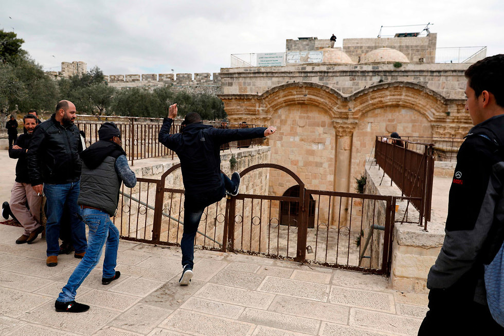 Palestinians trying to break down the locked gate at the Temple Mount compound (Photo: AFP)