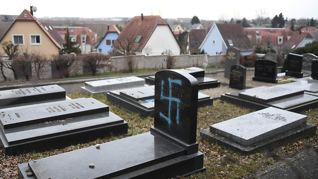 Graves desecrated with swastikas are seen in the Jewish cemetery in Quatzenheim, near Strasbourg, France, February 19, 2019 (Photo: AFP)
