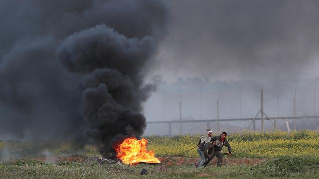 פלסטינים מפגינים בגבול הרצועה (צילום: רויטרס)