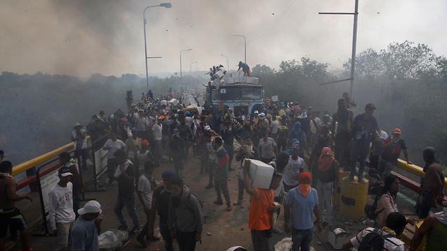 ונצואלה ציוד סיוע מ קולומביה משאית בוערת תושבים לוקחים קופסאות (צילום: רויטרס)