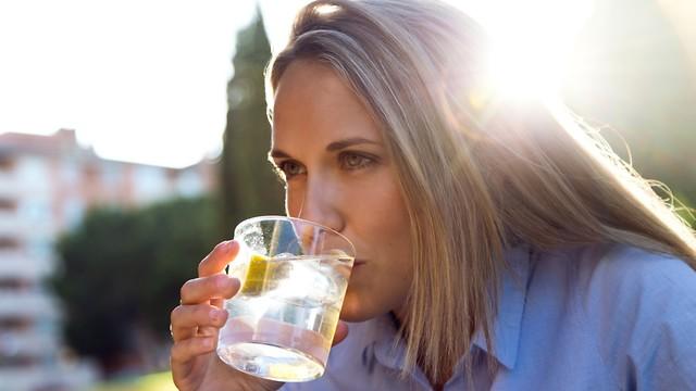 אישה שותה מים עם לימון (צילום: shutterstock)