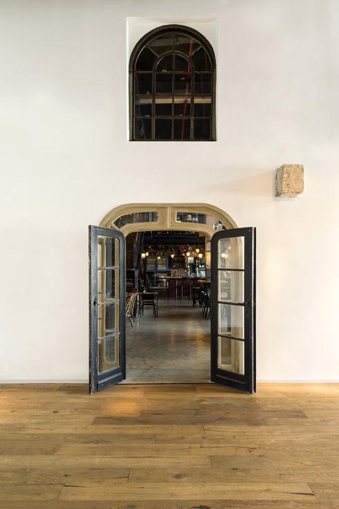 מבט מתוך הגלריה, דרך דלת המעבר, אל הבר (צילום: מושי גיטליס)