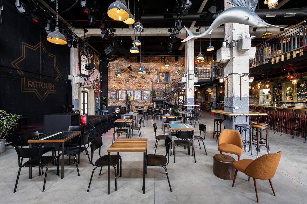 מבט מכיוון הכניסה אל האולם המרכזי של ''פטוש''. כאן יש בר ומסעדה עם פינות ישיבה מגוונות, בשתי קומות. משמאל במת הופעות, והקיר שבגבה - דומיננטי בזכות הצבע השחור וציורי הגרפיטי המקיפים דלת בסגנון אר-דקו - מפריד מאולם הגלריה הצמודה (צילום: מושי גיטליס)