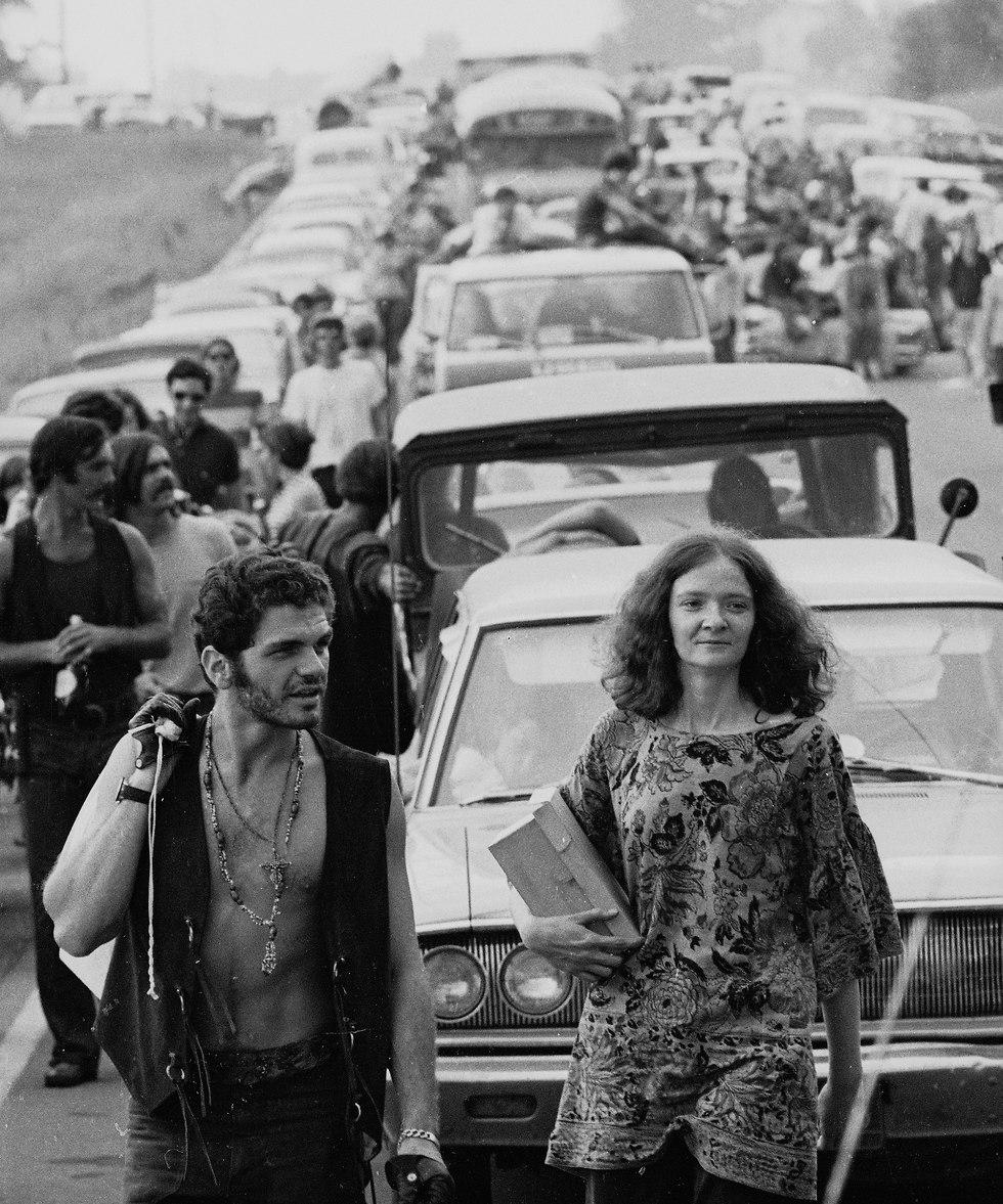 זוג הולך כשברקע תור ארוך של מכוניות (צילום: Getty Images)