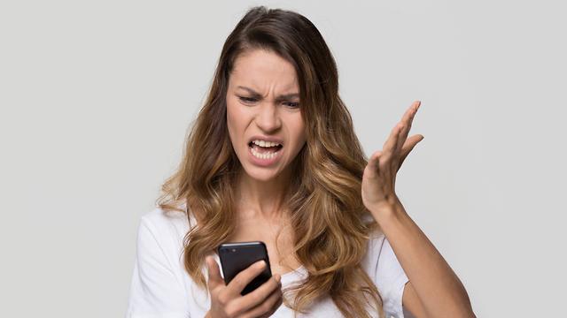 אישה מסתכלת על הטלפון וכועסת (צילום: Shutterstock)