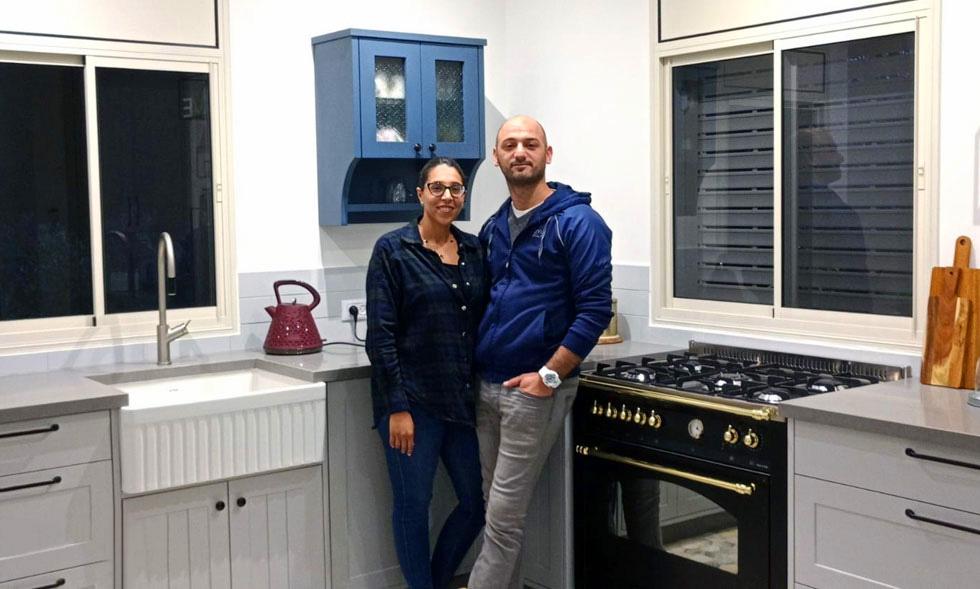 בני הזוג אוסמה וחנאן אגבאריה במטבח ביתם החדש. הוא אח במחלקה האורתופדית בתל השומר, היא עובדת משרד החינוך. יש להם שני בנים (5 ו-8). לשאלה אם לא באים אליהם בתלונות ובציפיות הם עונים: ''אמרנו את זה בהתחלה - אף אחד לא נכנס לנו לחיים'' (צילום: נדב גליק)