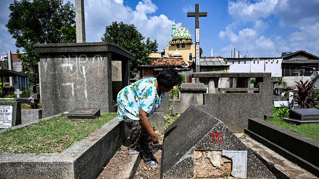 An Indonesian woman cleaning one of the Jewish tombs at a Christian cemetery in a Muslim majority neighborhood in Jakarta