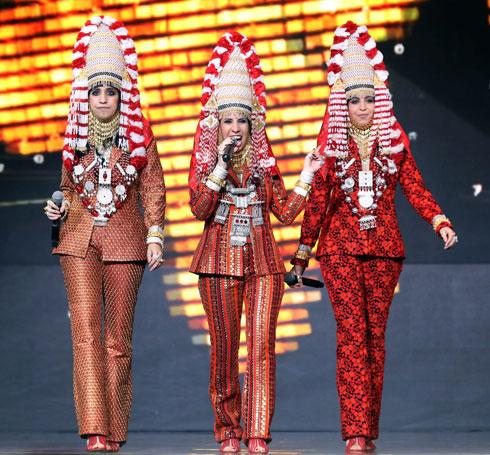 האחיות מההרכב A-WA בחליפות מכנסיים בעיצובה של חגית טסה, כשלראשן כובע התשבוק התימני מעוטר פרחים (צילום: סיון פרג')