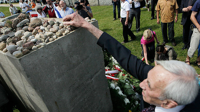 A visitor lays a stone at a memorial of the victims of the Jedwabne massacre  (Photo: AP)