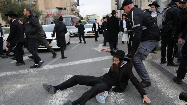 Haredi protester being evacuated from the road in Jerusalem (Photo: Alex Kolomoisky)