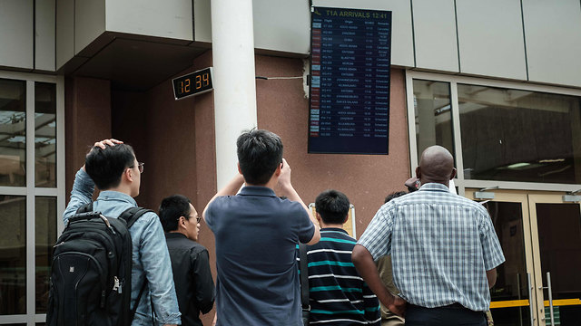 גברים ממתינים לעדכונים בנמל תעופה JKIA בניירובי, קניה (צילום: AFP)