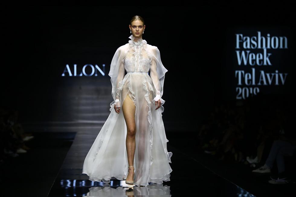 התצוגה נפתחה בחטיבה של שמלות כלה לבנות, שמצד אחד קרצו לכלות העתידיות של מותג האופנה, ומנגד יצרו אנטיתזה להמשך התצוגה האפלה (צילום: אלון פרס)