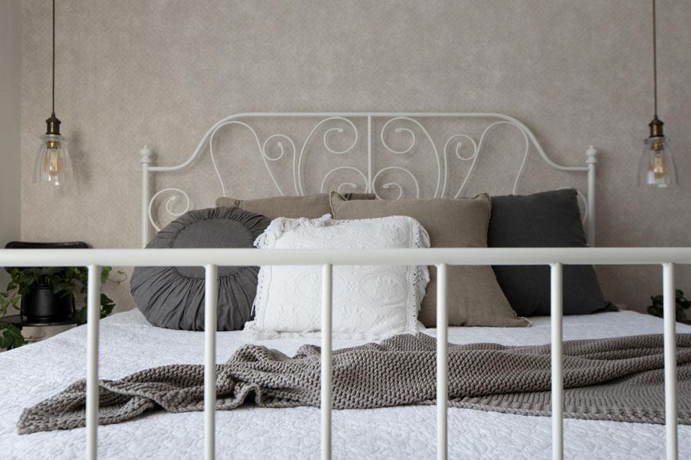את מיטת הברזל הלבנה הביאו בני הזוג מהבית הקודם. את המראה הרגוע משלימים ספסל עץ, מתלה במבוק לפריטים רומנטיים כלבבות ותמונות, ווילונות רכים, נשפכים (צילום: שירן כרמל)