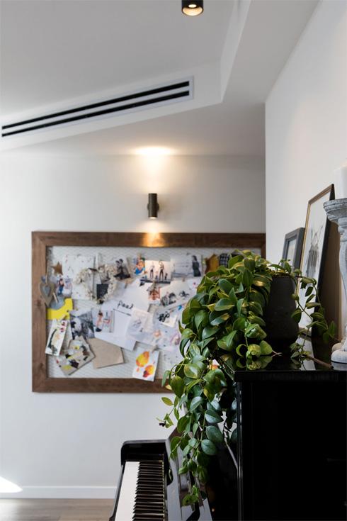מבט מהכניסה. פתקים, ציורים וצילומים על רשת ממוסגרת בעץ (צילום: שירן כרמל)