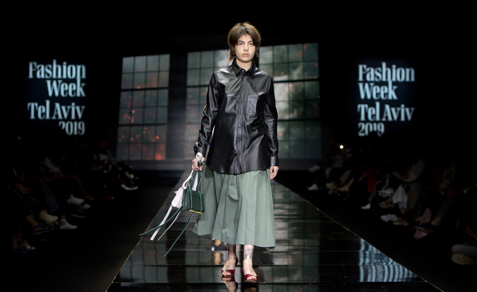 הדוגמנית מיה רו במערכת לבוש נהדרת, שהורכבה מחולצת כפתורים שחורה מעור עם חצאית מקסי בדוגמת פליסה בצבע אפור-ירקרק. שילוב היפר-מודרני שבחוגים מסוימים יכול להיתפש כסקסי (צילום: ענבל מרמרי)