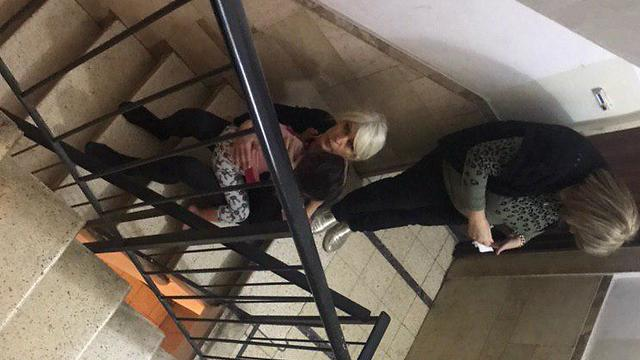 A woman holds a child in the stairwell of an apartment building during a rocket attack in central Israel