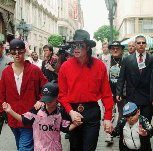 ג'קסון מלווה בילדים בעת ביקור בהונגריה בשיא תהילתו, 1996 (צילום: AP)