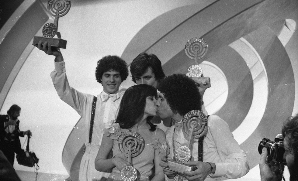 """חברי חלב ודבש (מלפנים: שמוליק בילו וגלי עטרי, מאחור: יהודה תמיר וראובן גבירץ) חוגגים על הבמה ומניפים את הפרס שהוענק להם - פסלון עץ בצורת הלוגו של רשות השידור שעליו נשענה מדליית זהב. למטה: אירוויזיון 1979, השידור המלא (צילום: צוות יפפ""""א, הספרייה הלאומית, ארכיון דן הדני)"""