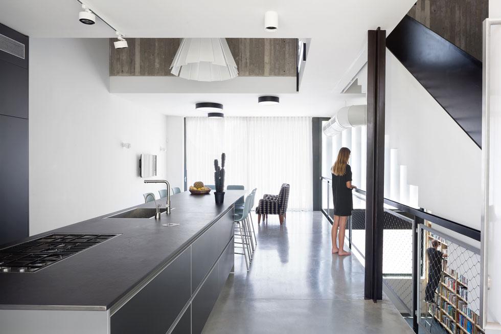 """לצד המטבח, מעבר למעקה הרשת, יש מרחב פתוח בגובה 13 מטרים, שמתחיל במרתף ומסתיים בגג. """"בשבת בבוקר אנחנו במטבח"""", מספר האב, """"וכשהבנות קמות הן יוצאות לגשר למעלה ואומרות 'הי'. זה כזה כיף"""". בהמשך המטבח יש פינת ישיבה קטנה עם טלוויזיה (צילום: שי אפשטיין)"""