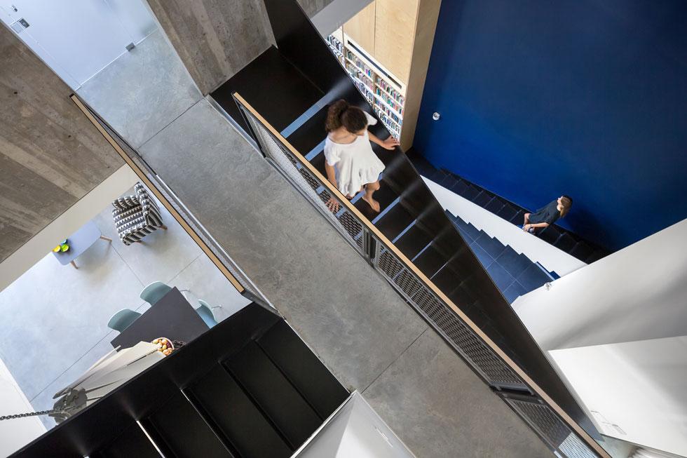 """גרמי המדרגות והגשרים מרחפים בחלל. """"בהתחלה היה סוג של פחד גבהים"""", מודה בעל הבית, """"אך אחרי כמה ימים מתרגלים"""". התכנון הייחודי מאפשר קשרי עין בין המפלסים השונים. במבט מהקומה העליונה ניתן לראות (משמאל) את קצה האי במטבח ואת פינת הישיבה  (צילום: שי אפשטיין)"""
