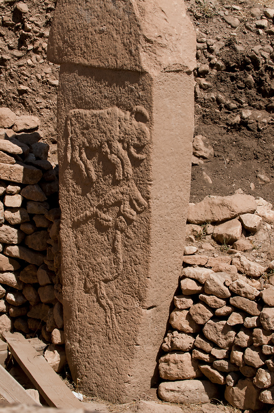 A pillar with what are believed to be reliefs of are believed to be a bull, fox, and crane