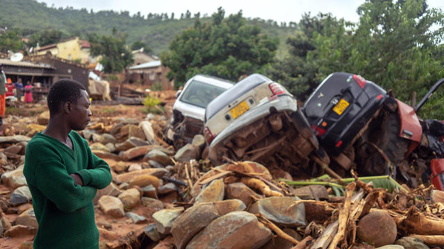 A man stands next to the wreckage a vehicles washed away in the Chimanimani, eastern Zimbabwe