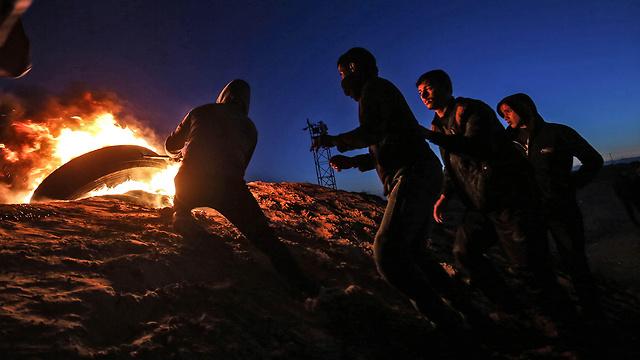 Palestinians protesting at night along the Gaza border fence (Photo: AFP)