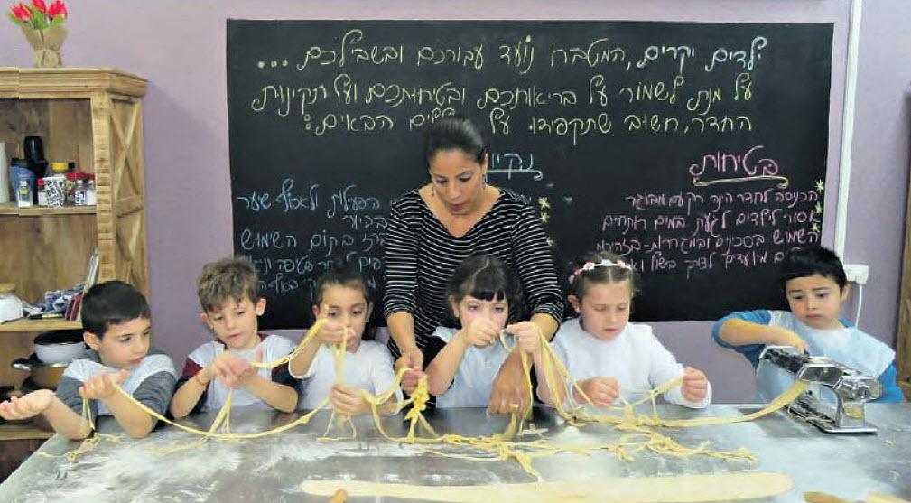 תלמידי בית-ספר ניצנים במודיעין והמורה אביבית לוי משלבים אפייה ומתמטיקה (צילום: עפרה גפן)
