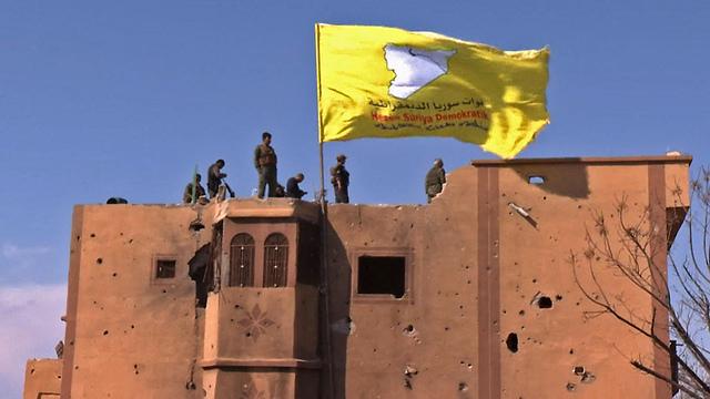 כוחות סורים מניפים דגל אחרי כיבוש מוצב של דאעש (צילום: AFP)