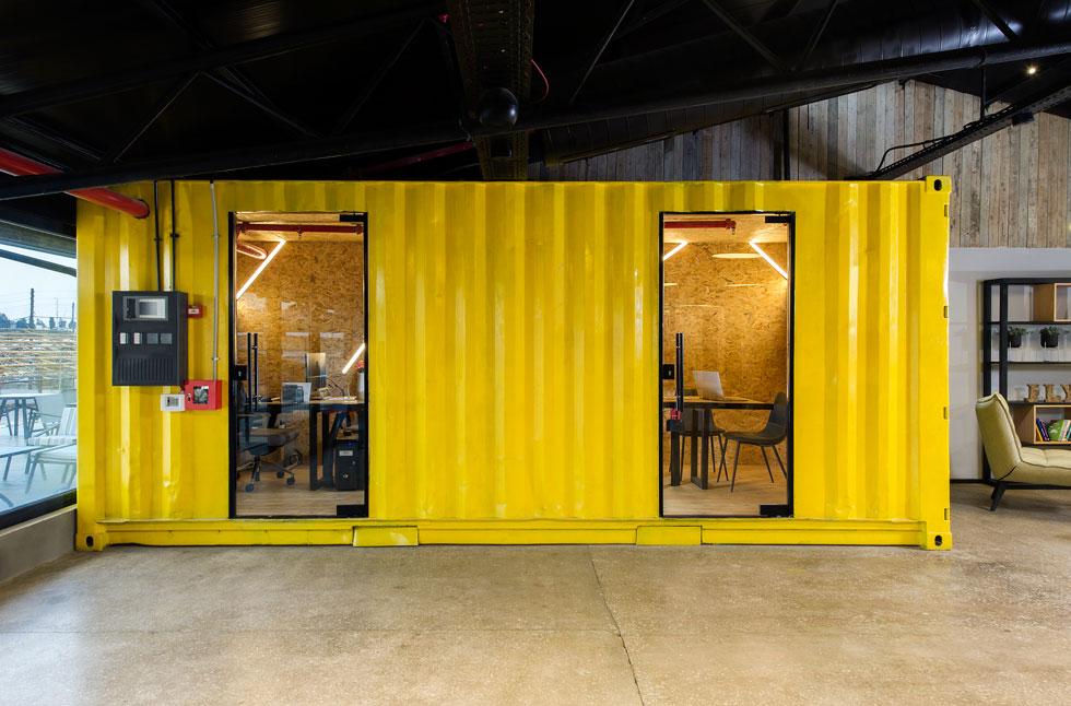 מכולה שהוצבה בחלל המרכזי נצבעה בצהוב, חופתה מבפנים בלוחות של שבבי עץ, ויש בה שני חדרי ישיבות מבודדים (צילום: מושי גיטליס)