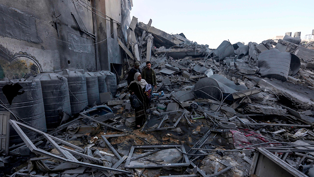 Palestinians inspect the damage caused by IAF strikes in Gaza, March 26, 2019  (Photo: AFP)