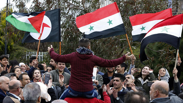 Syrians wave national flags as well as a Palestinain (L) and Syrian Social Nationalist Party (SSNP) (2 L) flags in the town of Quneitra in the Syrian Golan Heights